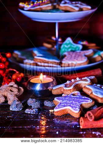 Candle light table with Christmas gingerbread cookies and cinnamon stick and star sweets are on decoration tiered cake stand wooden table and burning candles. Xmas still life object.