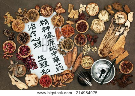Chinese herbal medicine with herbs, moxa sticks and acupuncture needles with script on rice paper. English translation reads as traditional ancient Chinese medicine to heal mind body and spirit.