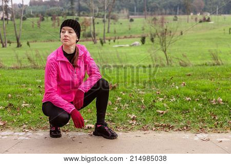 Young woman analyzing the track before running on a cold winter day on the training track of an urban park. Female athlete wearing pink windbreaker, beanie, gloves and running tights