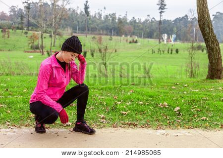 Young woman feeling lightheaded or with headache after train on a cold winter day on the training track of an urban park. Female athlete wearing pink windbreaker, beanie, gloves and running tights