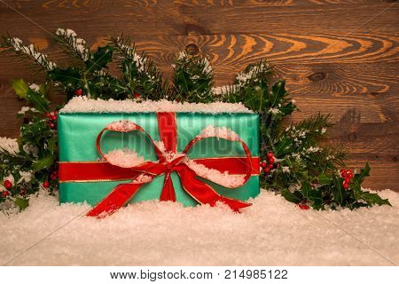 Christmas present gift wrapped in green paper with red ribbon with holly and snow against a wooden background, copy space for your own message.