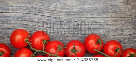 Bunches of red tomatoes, on wooden table, with copy space