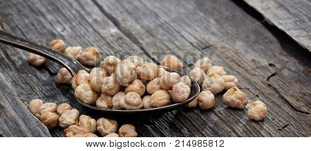 Raw chickpeas on an old wooden table, copy space