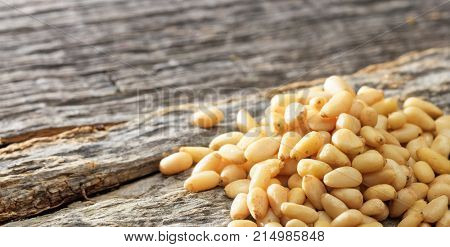 Dried pine nuts seeds set on an old wooden surface, copy space