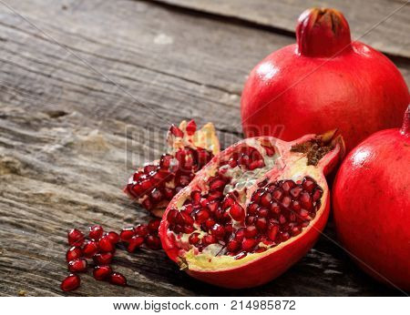 Pomegranates on a wooden table, copy space