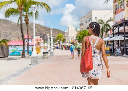 Philipsburg St Maarten woman tourist walking in shopping street, cruise ship travel destination. Caribbean tropical island hopping vacation holiday. Girl with purse bag visiting town.