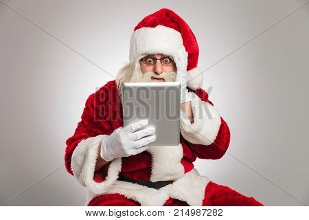 santa claus is reading something shocking on his tablet pad computer on grey background