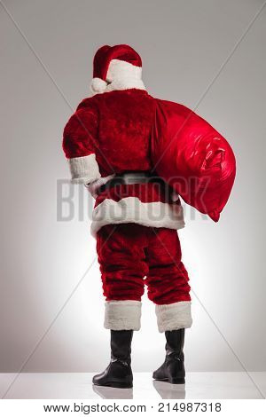 back view of santa claus with bag on shoulder and hands on waist looking awy from the camera