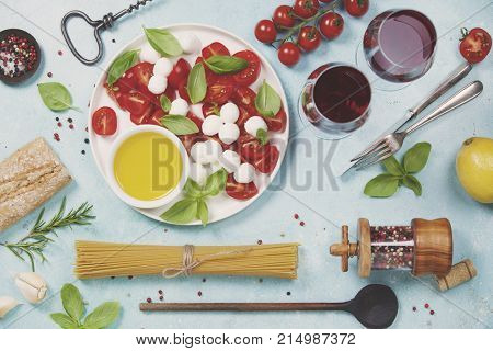 Italian food background. Mozzarella cheese, fresh basil leaves, tomatoes, olive oil, spaghetti and glasses of red wine on concrete background, top view. Caprese salat ingredients