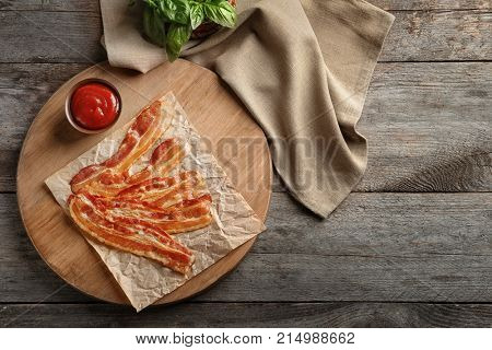 Board with cooked bacon rashers on wooden table