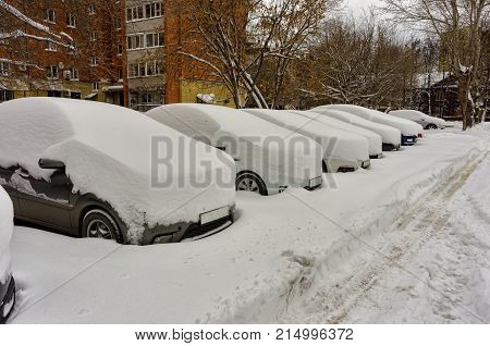 Cars covered with fresh white snow on city parking lot