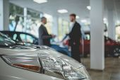 Auto showroom, dealer talking with buyer. Electro cars in moderm vehicle salon. poster