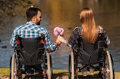 A couple of invalids on wheelchairs met in the park. A man and a woman are holding a bouquet of flowers. They are sitting on the shore of the lake. poster