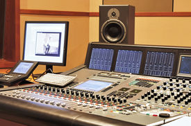Shot of a recording studio, complete with technition and equipment.
