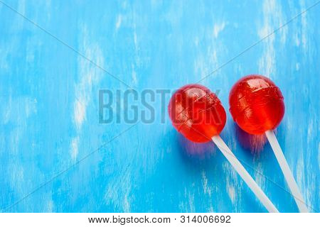 Two Red Lollipops On White Sticks. In The Right Down Corner On The Blue Background. Red And Blue, Lo