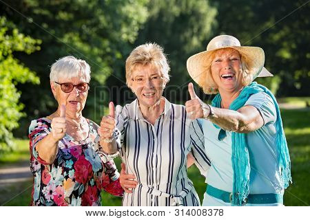 Three Positive Elderly Women Are Standing Arm In Arm, Optimistic Smiling And Showing The Thumbs Up.