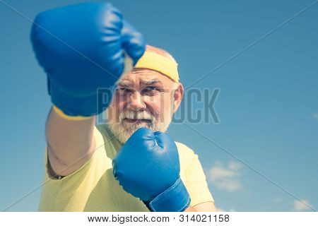Fighter. Boxer With Boxing Glove. Senior Man In Gloves Beats Punching Bag. Boxing. Older Man Boxing.