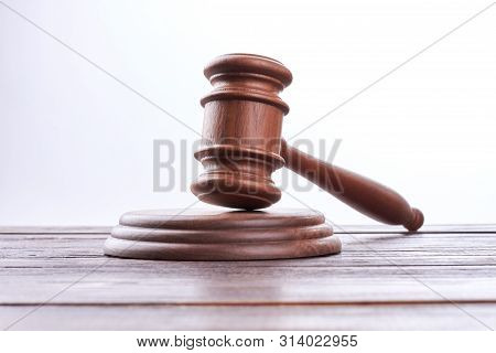 Wooden Gavel Over White Background. Jude Gavel On Brown Wooden Table. Law, Justice And Auction.