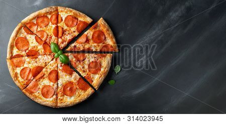 Tasty Pepperoni Pizza On Black Concrete Background. Top View Of Hot Pepperoni Pizza. With Copy Space