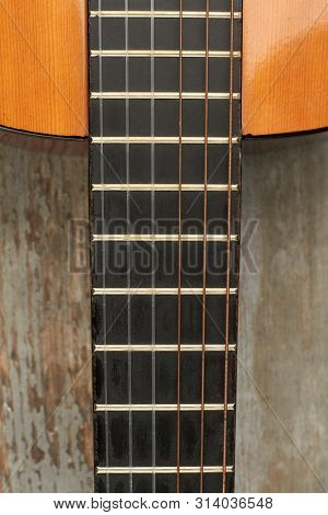 Acoustic Guitar Fretboard. Guitar On Wooden Background With Fretboard And Strings Close Up, Vertical