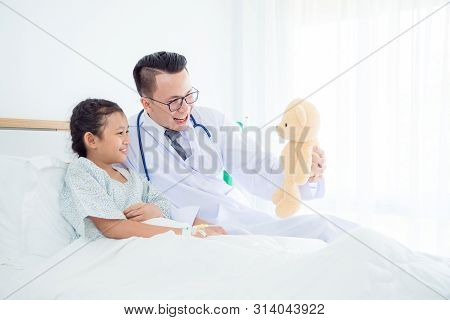 Pediatrician Male Doctor Holding Teddy Bear And Playing With Child Patient Who Lying On Hospital Bed