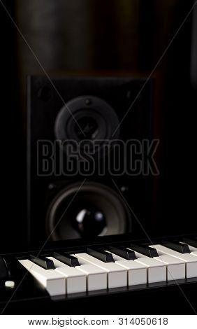 Piano Keys And Audio Speaker Closeup On Dark Background