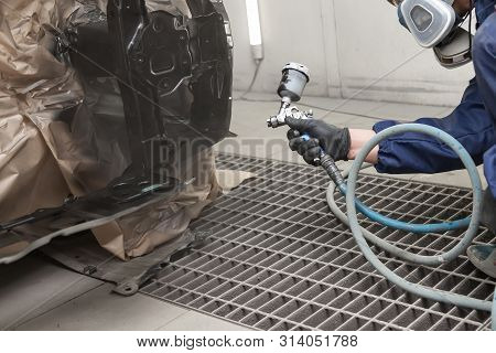 A Male Worker In Jumpsuit And Gloves Paints With A Spray Gun A Front Frame Part Of The Car Body In B