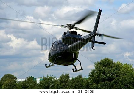 Black Helicopter Taking Off Above The Trees