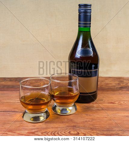 Two Portion Of Brandy In Brandy Bowls And Bottle Of Brandy On The Old Wooden Rustic Table
