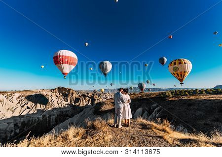 Couple Travels The World. Happy And Loving Couple Among Balloons In Turkey. Married Couple On Vacati