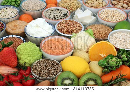 Vegan health food selection with tofu bean curd, fruit, vegetables, grains, legumes, nuts, seeds, almond butter & yoghurt. Super foods high in antioxidants, dietary fibre, omega 3 & vitamins.