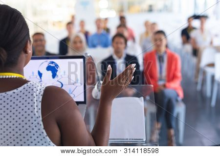 Rear view of pretty African-american female speaker giving speech to diverse people in a business seminar. International diverse corporate business partnership concept