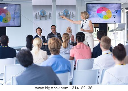 Side view of Caucasian female speaker giving presentation in a business seminar. International diverse corporate business partnership concept