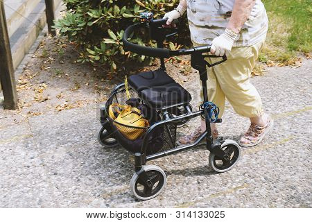 Elderly Woman Walking Outside With Rollator Or Wheeled Walker - Authentic Real People Concept
