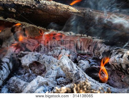 Background Of Fireplace With Gloving Embers. Close Up View On Smouldering Fire. Embers Burning With