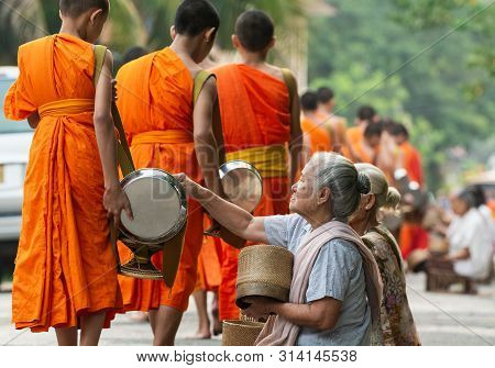 Luang Prabang, Laos - May 2019: Laotian People Making Offerings To Buddhist Monks During Traditional