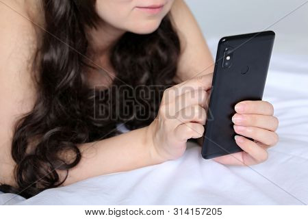 Woman With Long Curly Hair Lying On A Bed And Using Smartphone. Mobile Phone In Female Hands, Concep