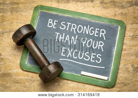 Be stronger than your excuses - fitness motivation quote on a slate blackboard with qn iron dumbbell
