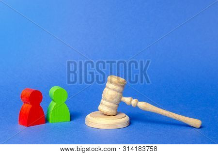 Two Figures Of People Opponents Stand Near The Judge's Gavel. The Judicial System. Court Case, Settl