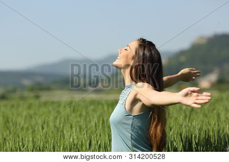 Side View Portrait Of A Happy Woman Breathing Deeply Fresh Air In A Green Field