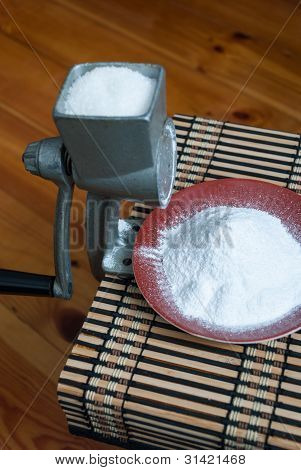 Powdered sugar mill and on the background of the wooden mats. Side view. poster