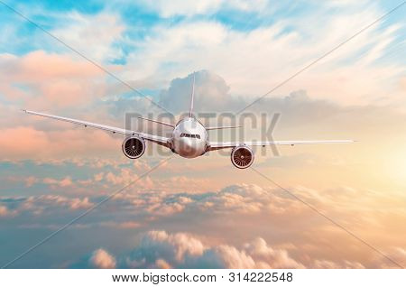 Airplane Flying Above Evening Light Above The Clouds At Sunset
