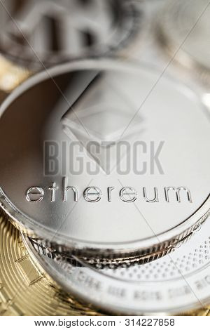 Ether Physical Coin On The Stack Of Other Different Cryptocurrencies. Close-up Photo Of Ether With S