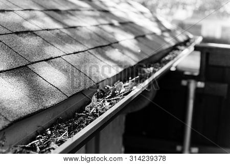 Filtered image gutter clogged by dried leaves and messy dirt need clean-up poster