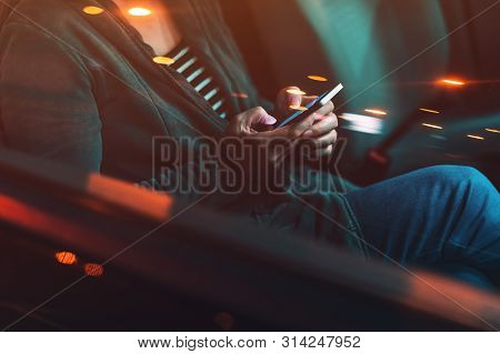 Woman Texting On Mobile Phone In Car At Night On A Parking Lot, Adult Female Person Using Smartphone