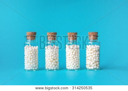 Homeopathic Globules In Four Glass Bottles On Blue Background. Alternative Homeopathy Medicine Herbs