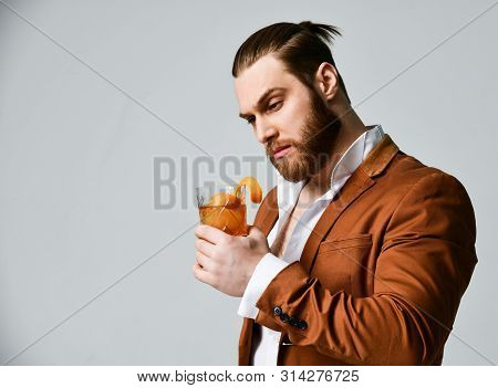 Picky Modern Man Bearded Clubber In Fashion Suit Looks Skeptically At The Glass With Fresh Cocktail