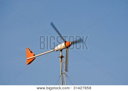 Wind turbine on the blue sky field.