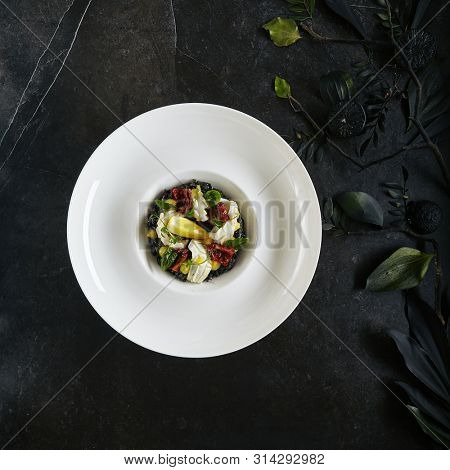 Exquisite Serving White Restaurant Plate of Black Risotto with Octopus and Sun Dried Tomatoes Top View. Delicacy Cuttlefish or Squid Meat with Greens and Lemon on Natural Black Marble Background poster