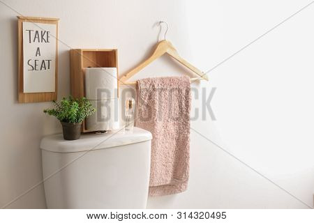 Decor elements, necessities and toilet bowl near white wall, space for text. Bathroom interior poster
